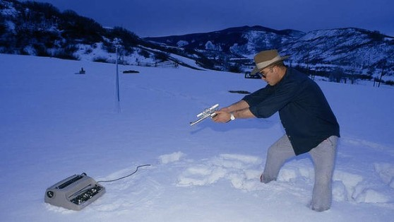 Hunter S. Thompson takes aim at a typewriter.